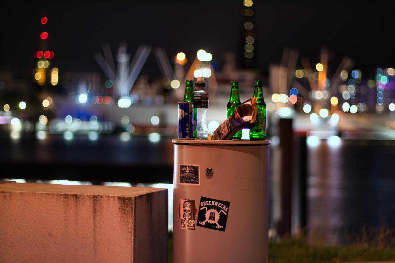 Bild verdeutlichtet das Leben in Hamburg bei Nacht. Ein voller Mülleimer vor der Kulisse der Landungsbrücken